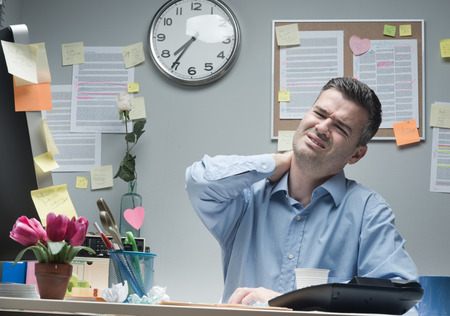 over burdened: Tired businessman sitting at desk touching his painful neck.