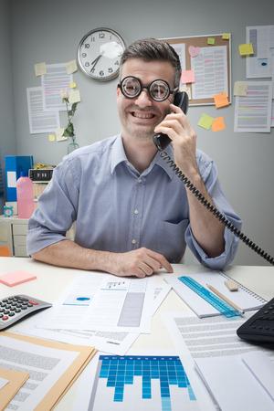 caricaturas de personas: Oficinista del empollón en el teléfono que se sienta en el escritorio y sonriente. Foto de archivo