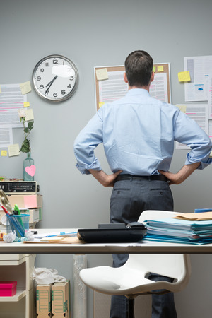 arms akimbo: Office worker standing at workplace looking at notes on pin board.