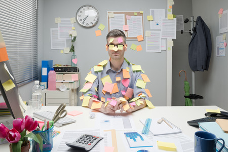 burdened: Office worker sitting at desk covered with colorful post it stick notes.
