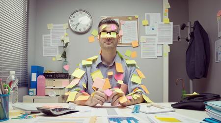 over burdened: Office worker sitting at desk covered with colorful   stick notes.