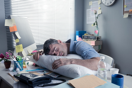 over burdened: Exhausted businessman sleeping at workplace with a pillow on his desk.