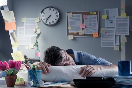 cuarto desordenado: Hombre de negocios agotado que duerme en el lugar de trabajo con una almohada sobre su escritorio.