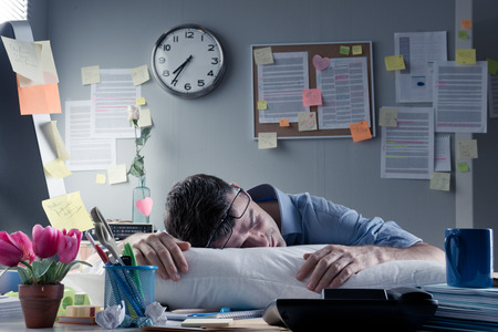 Uitgeput zaken man slapen op de werkplek met een kussen op zijn bureau. Stockfoto