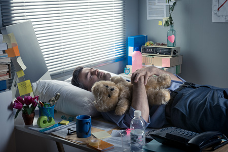 over burdened: Office worker sleeping at workplace with teddy bear and pillow.