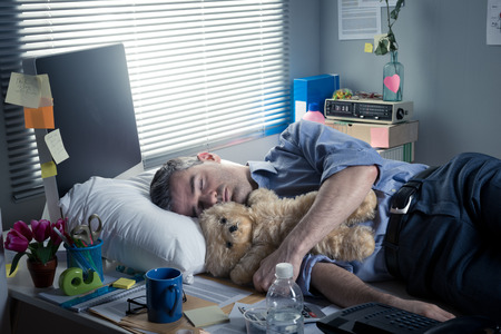 Office worker sleeping at workplace with teddy bear and pillow. photo