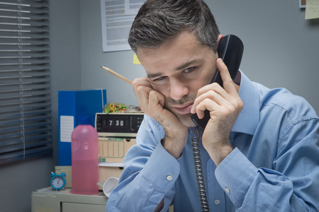 Tired stressed businessman on the phone at his office desk. photo