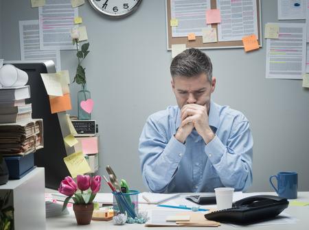 oficina desordenada: Hombre de negocios pensativo en el escritorio con las manos juntas mirando hacia abajo.