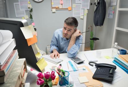 oficina desordenada: Deprimido oficinista aburrido en su escritorio la celebración de gafas.