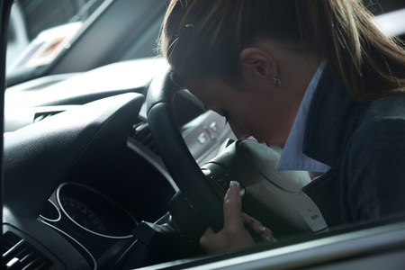 over burdened: Depressed young woman sitting in a car leaning to steering wheel.