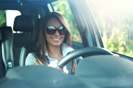 beautiful long hair: Attractive business woman with sunglasses smiling and driving her car. Stock Photo