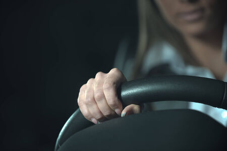 unrecognizable: Woman driving a car late at night, hands on steering wheel close-up.