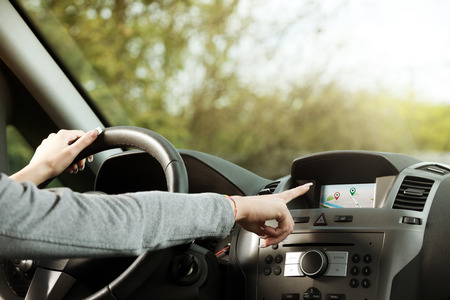 sat: Woman driving and using touch screen gps panel for navigation in a car. Stock Photo
