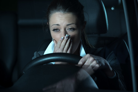 Distracted exhausted woman driving a car late at night. Standard-Bild