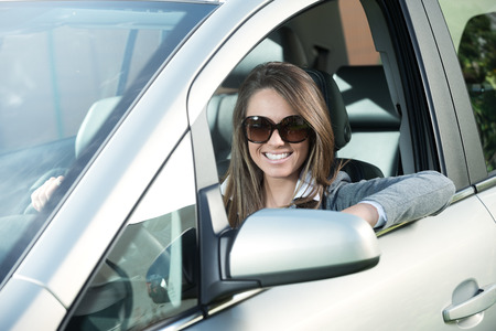 business fashion: Attractive woman wearing sunglasses, driving her car and smiling.