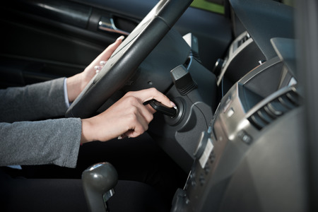 Female driver hand inserting car key and starting engine. Stock Photo