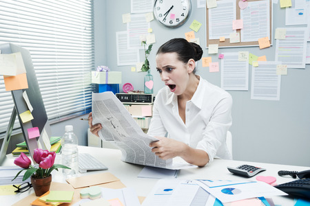 Shocked businesswoman mouth open reading financial news at office desk. photo
