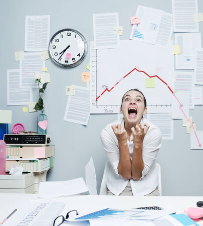 insane: Shocked businesswoman screaming under financial negative diagram with arrow going down. Stock Photo