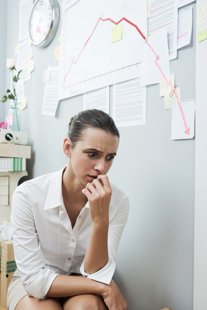 kneeling woman: Stunned businesswoman checking a financial business chart on office wall with arrow going down.