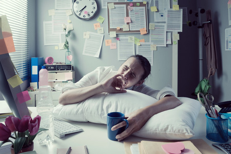 Tired businesswoman at office desk waking up with pillow and coffee. photo