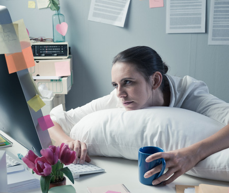 Overworked office woman with pillow working at computer. photo