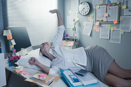 messy desk: Tired businesswoman waking up on office desk with pillow. Stock Photo
