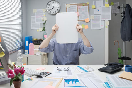 Office worker hiding behind a white blank sign in a small office. photo