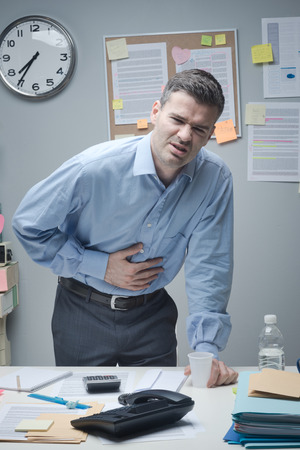 indigestion: Stressed businessman with stomachache leaning to his desk.