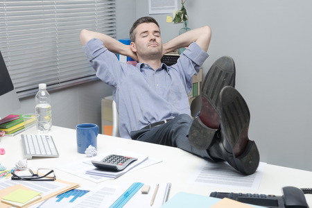 Lazy office worker feet up relaxing in his small office. Stock Photo - 33304598