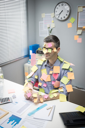 overburdened: Office worker sitting at desk covered with colorful  stick notes.