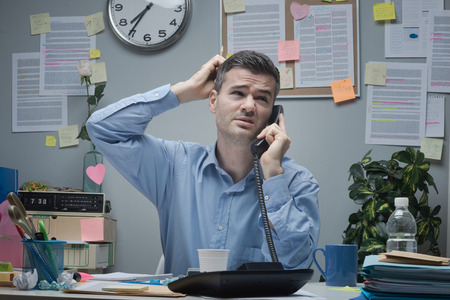embarassment: Confused employee on the phone at office desk touching his head. Stock Photo