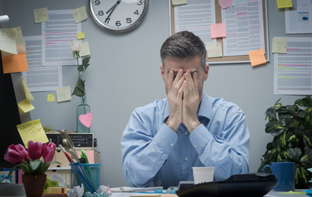 stress: Exhausted office worker with head in hands sitting at his office desk.