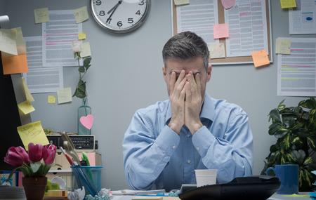 empleado de oficina: Oficinista agotado con la cabeza en las manos sentado en su escritorio de oficina.