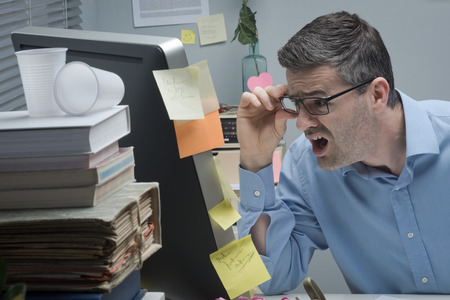 Shocked businessman staring at computer screen with mouth open. photo