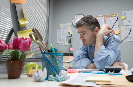 Depressed bored office worker at his desk holding glasses.
