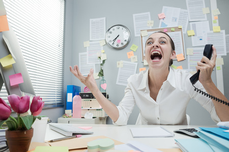 phone receiver: Angry stressed businesswoman in office shouting at phone.