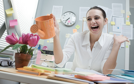 desk clerk: Young cheerful woman at work watering pink flowers on her desk.