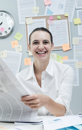 financial newspaper: Cheerful female white collar in office desk reading good news on financial newspaper.