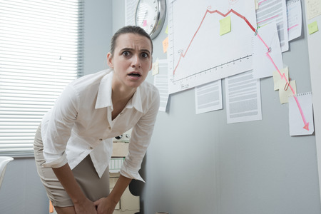 Stunned businesswoman checking a financial business chart on office wall with arrow going down. photo