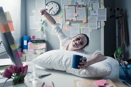 Smiling businesswoman waking up in office and stretching. Stock Photo