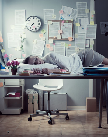 messy desk: Tired businesswoman sleeping in office overnight with pillow on desk.