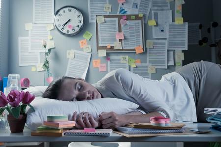 overnight: Tired businesswoman sleeping in office desk overnight.
