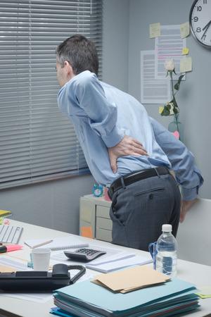 疲れたビジネスマン彼の机に傾いていると痛みを伴う腰に触れます。 写真素材