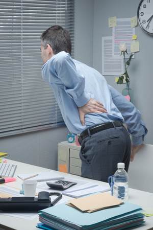 lower back: Tired businessman leaning to his desk and touching his painful lower back.