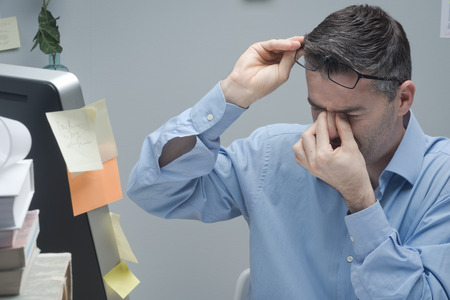 Office worker with eye pain touching his eyes and holding glasses.