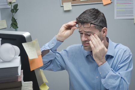 Office worker with eye pain touching his eyes and holding glasses. photo