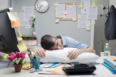 疲れのサラリーマンが彼のオフィスの机の上の枕で寝ています。 写真素材
