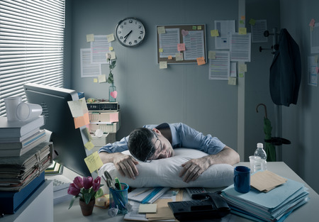 Exhausted businessman sleeping at workplace with a pillow on his desk.