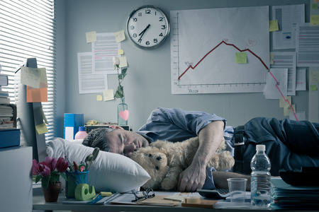 overnight: Funny office worker sleeping in the office overnight with teddy bear.