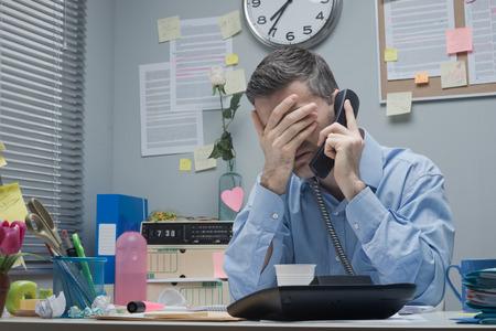 彼の額に触れる電話で従業員を強調しました。 写真素材